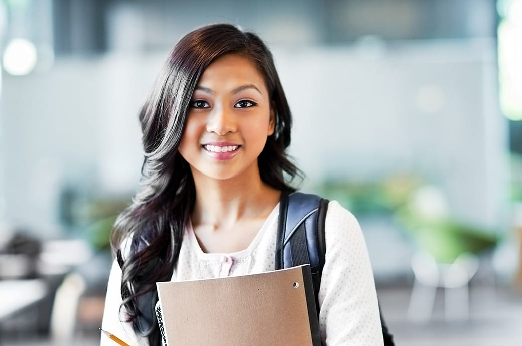 A smiling teen wearing a backpack and carrying her notebooks